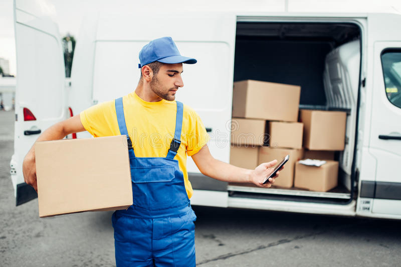 Cargo delivery service, courier with box and phone. Cargo delivery service, male courier in uniform with box and mobile phone in hands. Empty container stock images