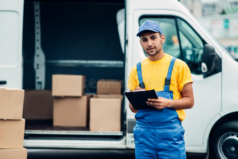 Cargo delivery service, male courier unload truck. Cargo delivery service, male courier in uniform with box in hand unloads truck with cardboard parcels. Empty stock images
