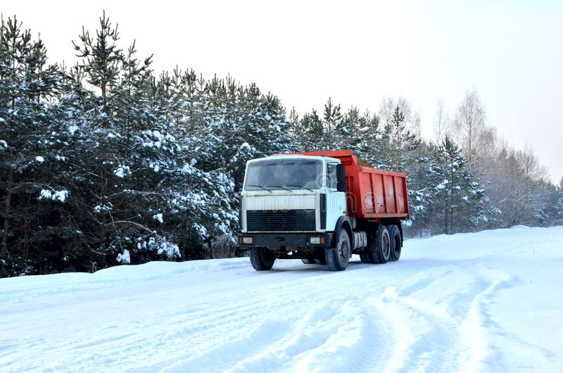 Cargo dump truck rides on a snowy road to load sand into career. Winter road against the backdrop of fabulous spruce trees. In the snow and blue sky stock image