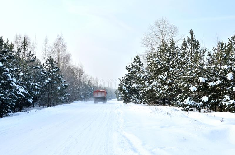 Cargo dump truck rides on a snowy road to load sand into career. Winter road against the backdrop of fabulous spruce trees. In the snow and blue sky royalty free stock photos