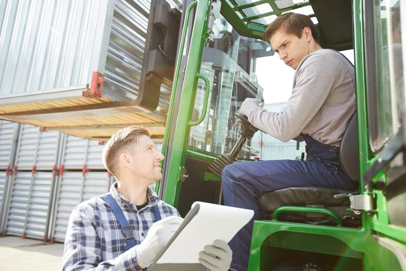 Cargo foreman talking to young forklift driver stock photos