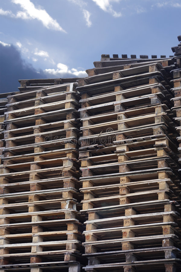 Cargo pallets with sky. Stacks of used wooden cargo shipping pallets stock photography