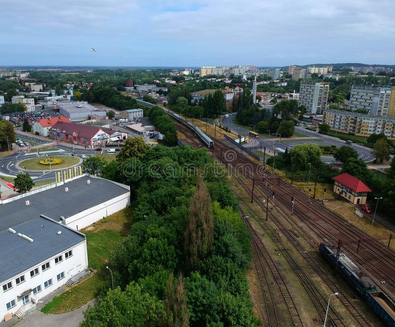 Cargo and passenger wagons on train station in city, aerial view, road roundabout intersection with bridge.  royalty free stock photo