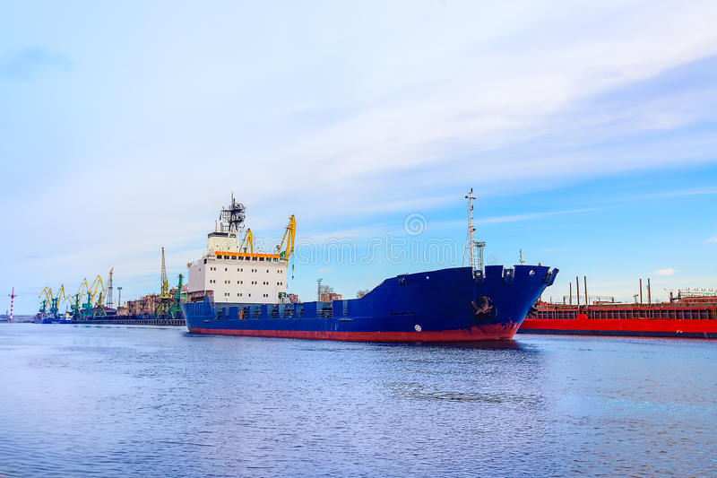 Cargo port. The ship is blue. Front view. stock image