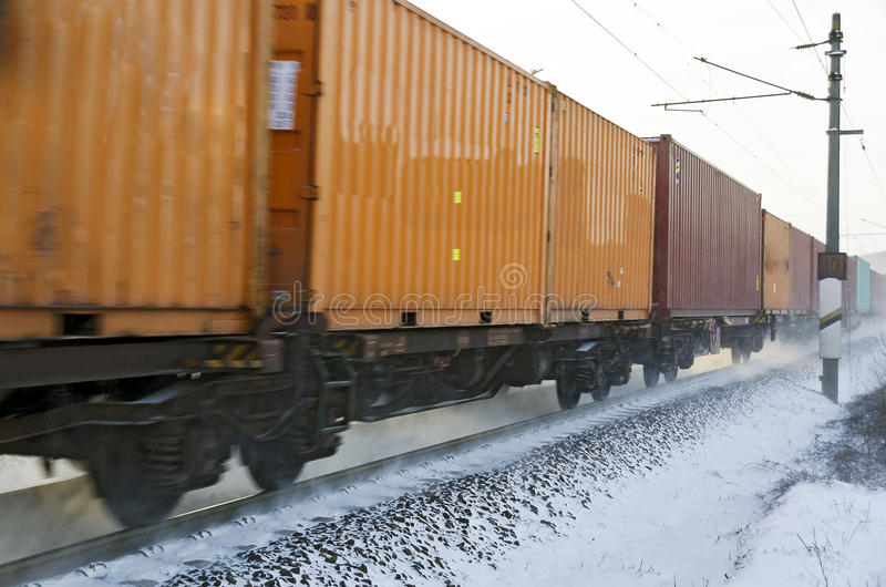 Cargo rail with container wagons. Running on winterly snowy track stock photography