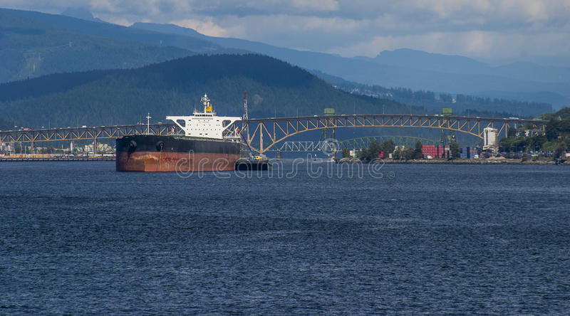 Cargo ship at anchor in Burrard Inlet. With Second Narrows bridge and old railway bridges in the background royalty free stock images