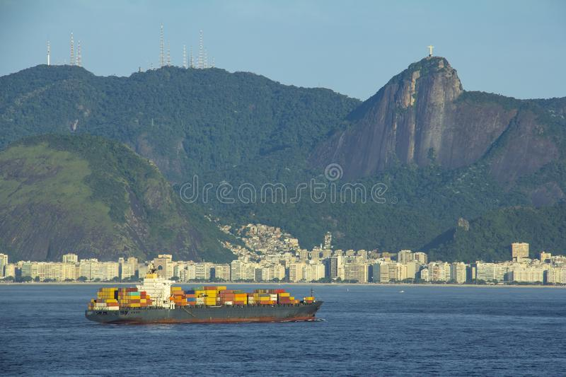 Cargo ship arriving in Rio de Janeiro with the statue of Christ the Redeemer, mountains, hills and Copacabana beach royalty free stock photo