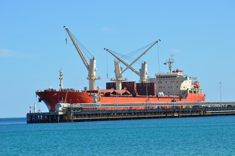 Cargo ship being loaded royalty free stock image
