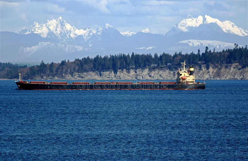 Cargo Ship in Blue Water with Snow-Capped Mountains royalty free stock photo