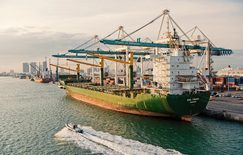 Cargo ship with cranes in sea port. Maritime container port or terminal. Shipping, freight, logistics, merchandise royalty free stock photos