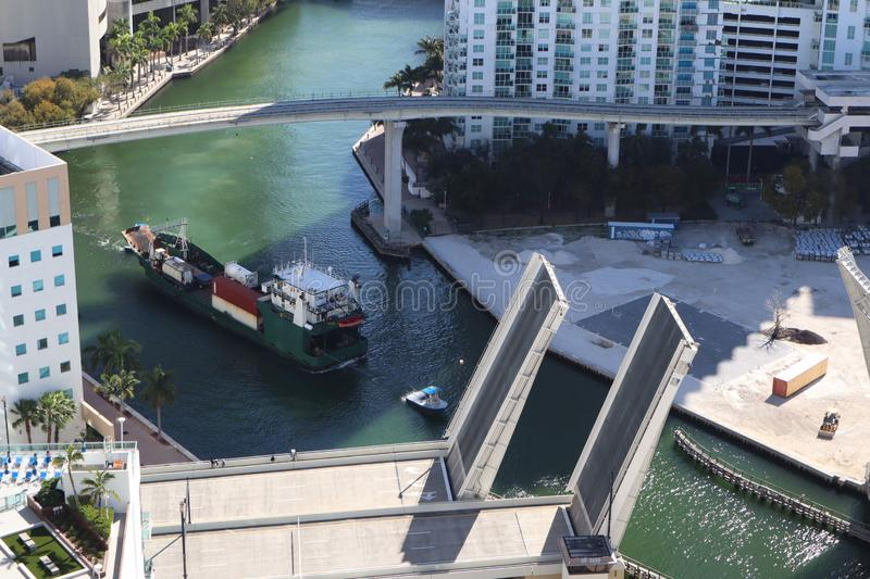 Cargo ship entering the Miami River in Downtown Miami. A divorced bridge. Passage of a cargo ship under the bridge. Taken from the. Air royalty free stock image