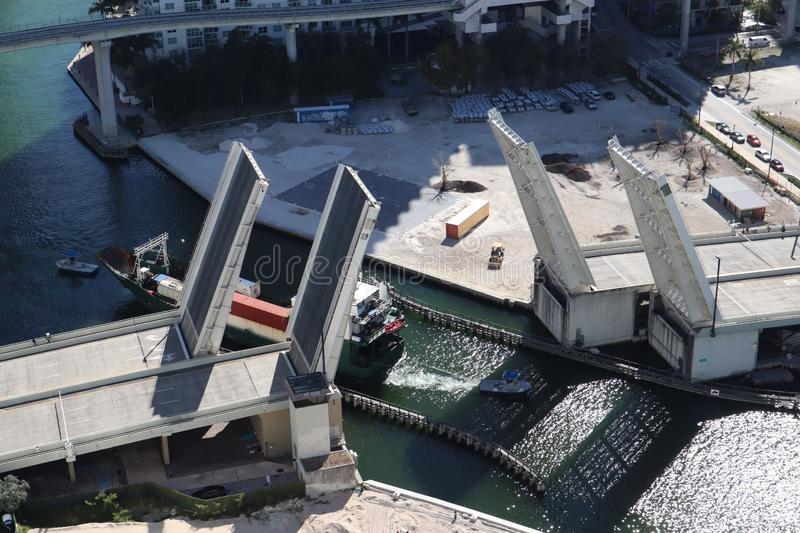 Cargo ship entering the Miami River in Downtown Miami. A divorced bridge. Passage of a cargo ship under the bridge. Taken from the. Air stock photography