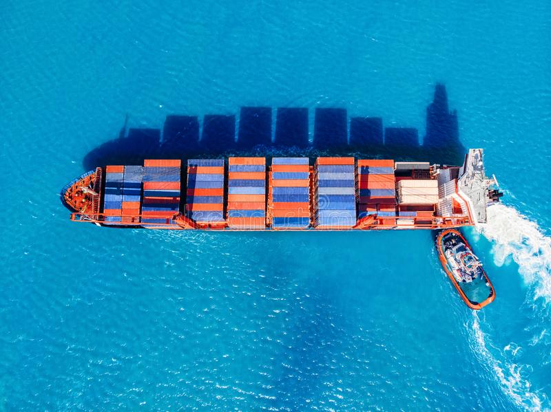 Cargo ship enters trading port, tug helps moor to pier. Logistics concept, transport sea stock images