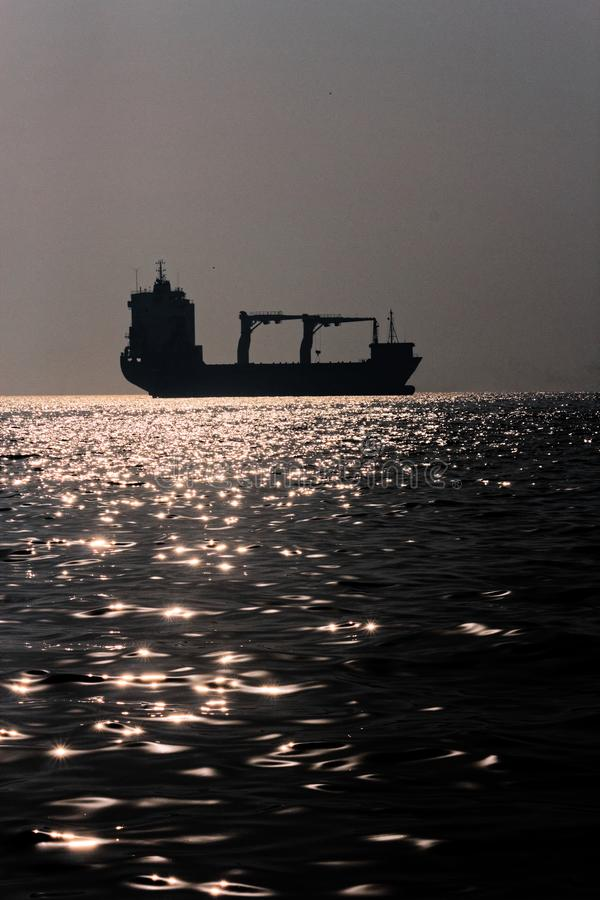 Cargo Ship on high seas. Silhouette of a large Cargo Ship on the high seas in Mumbai, India stock image