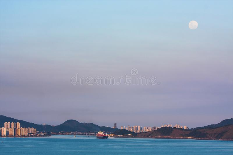 Cargo ship leaving the port of Santos during sunset with a full moon rising stock images