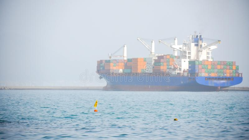 Cargo ship with multiple containers floats in the sea far away. Shot from away stock images