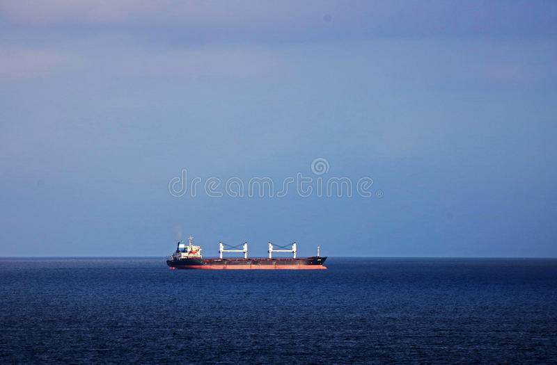 CARGO SHIP OFF SHORE IN THE LIGHT OF THE SUN. Image of cloudy sky and blue Indian ocean with view of a cargo ship with the light of the sun focused on it royalty free stock photos