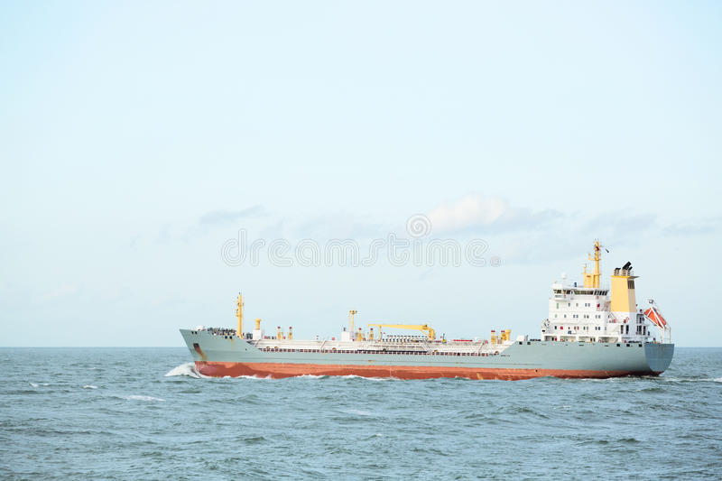 Cargo Ship in Open Water. A small cargo ship in open water with clear sky stock photo