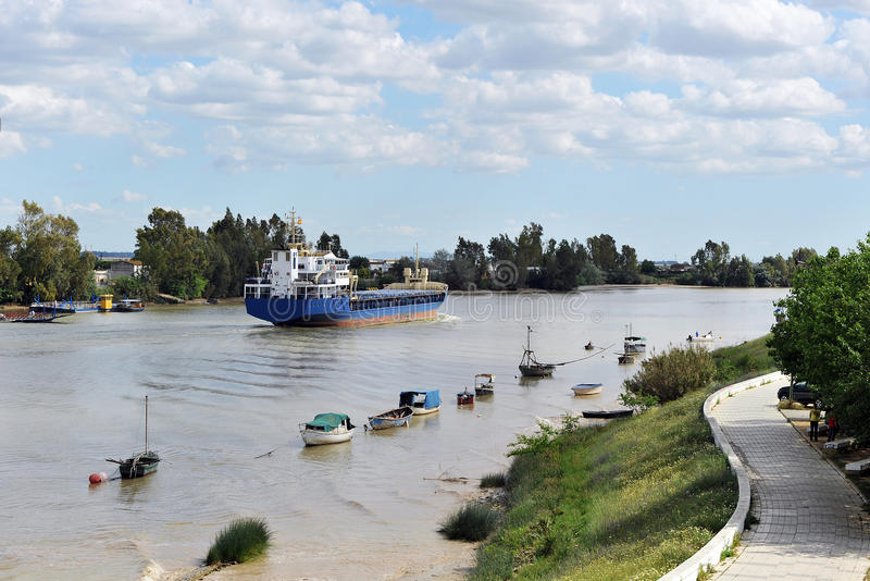 Cargo ship on the river Guadalquivir in its passage through Coria del Río, Sevilla, Andalucía, Spain. Cargo ship sailing on the river Guadalquivir as it stock photo