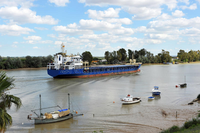 Cargo ship on the river Guadalquivir in its passage through Coria del Río, Sevilla, Andalucía, Spain. Cargo ship sailing on the river Guadalquivir as it stock photography