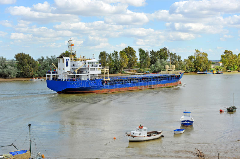 Cargo ship on the river Guadalquivir in its passage through Coria del Río, Sevilla, Andalucía, Spain. Cargo ship sailing on the river Guadalquivir as it stock image