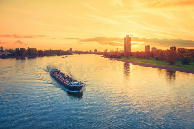 Cargo ship in the river Rhine. Cologne, Germany at orange sunset stock photo