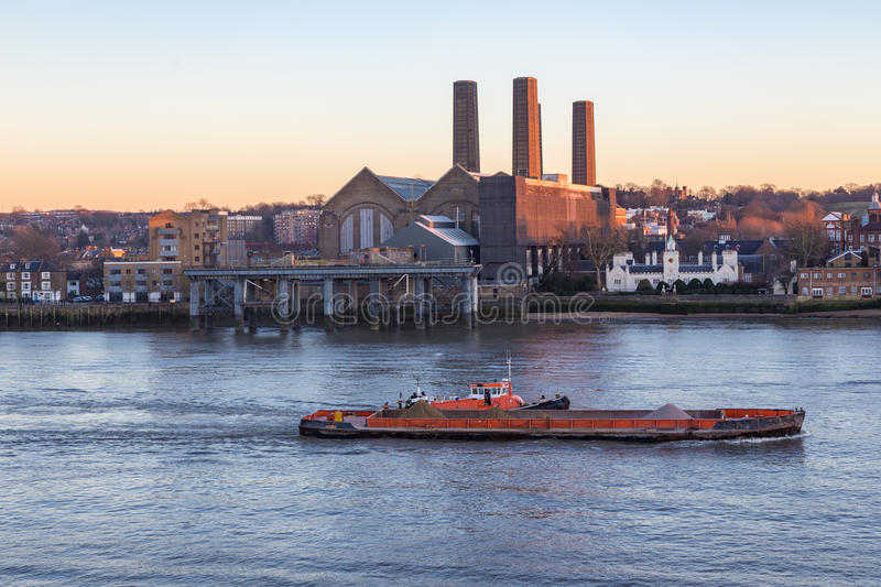 Cargo ship on the River Thames at the Greenwich power station. stock photos