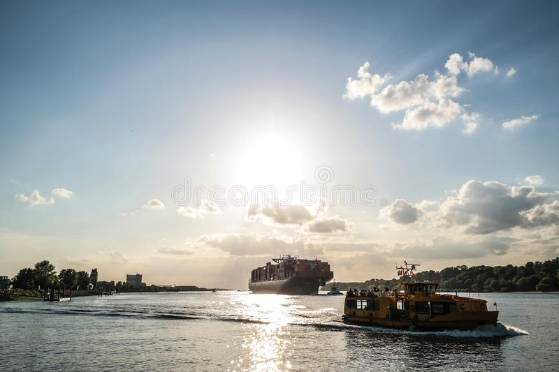 Cargo ship in sunlight. Large container ship and vessels on water under blue sky with light clouds royalty free stock photography