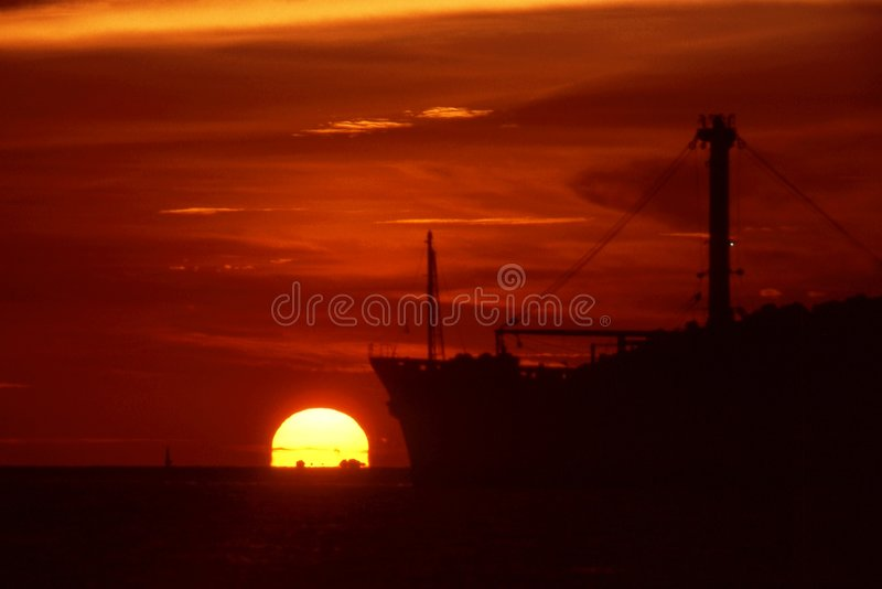 Cargo ship and sunset. royalty free stock photos