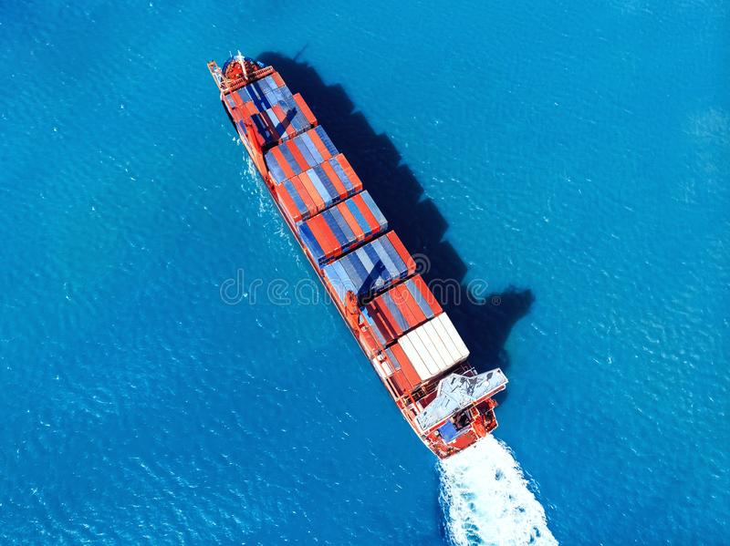 Cargo ship transporting containers import export to port on background of blue sea. Top view Aerial. Logistics concept.  stock photography