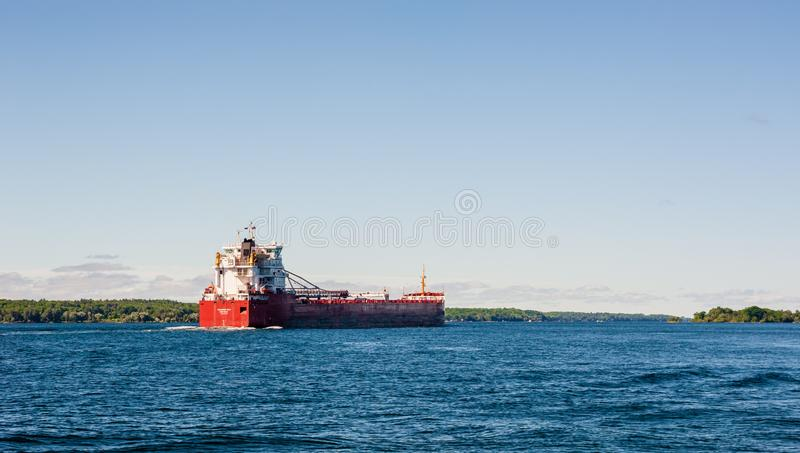 Cargo ship travelling along wide river near Brockville, Ontario, Canada. BROCKVILLE, CANADA - JUNE 19, 2018: The lake freighter `Thunder Bay` travels along the royalty free stock image
