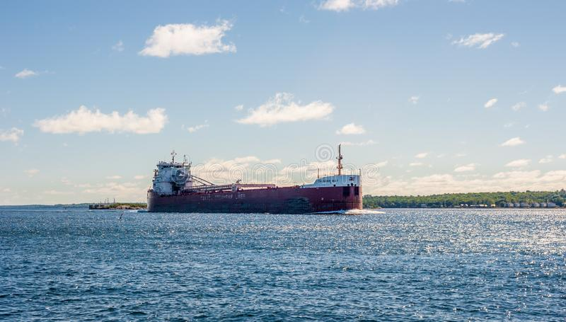 Cargo ship travelling along wide river near Brockville, Ontario, Canada. BROCKVILLE, CANADA - JUNE 19, 2018: The lake freighter `Thunder Bay` travels along the royalty free stock photos