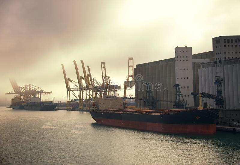 Cargo Ship Unloading At The Port Stock Photo