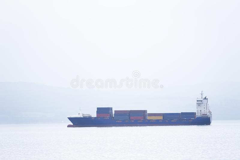 Cargo ship vessel freight containers carrier transport on sea ocean to port dock. Uk royalty free stock photos