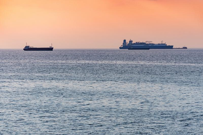 Cargo ships and barge at beautiful sunset. Amazing evening seascape, breathtaking travel view, copy space. Anchorage for ships royalty free stock photo