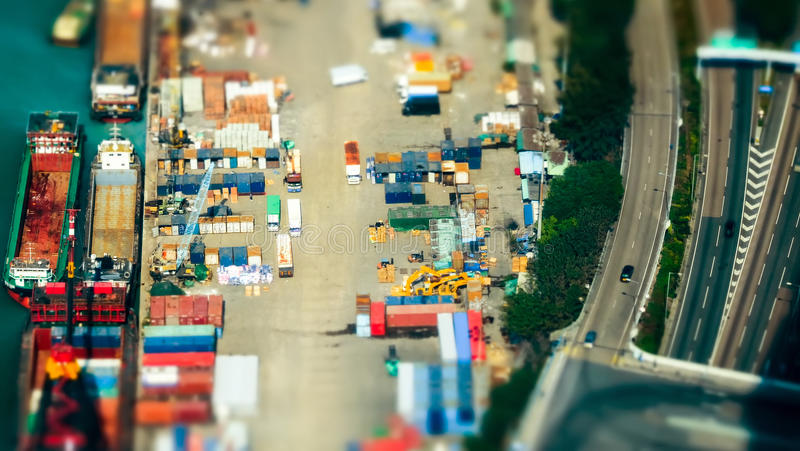Cargo ships with containers at port terminal. Hong Kong. Tilt shift. Tilt shift blur effect. Aerial view cargo ships loaded by crane with cargo containers at a royalty free stock photos