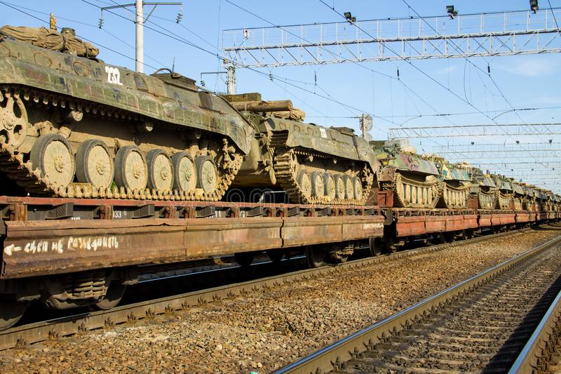 Cargo train carrying military tanks on railway flat wagons. Cargo train carrying military tanks on a railway flat wagons royalty free stock images