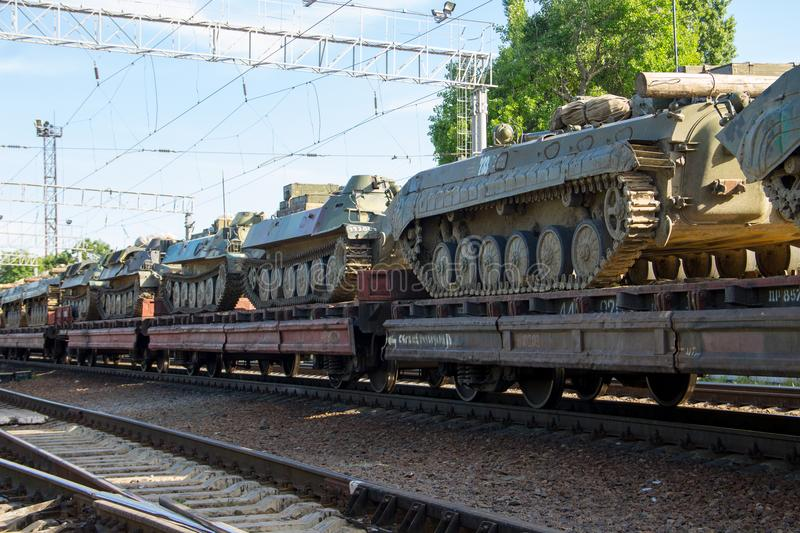 Cargo train carrying military tanks on railway flat wagons. Cargo train carrying military tanks on a railway flat wagons stock photography