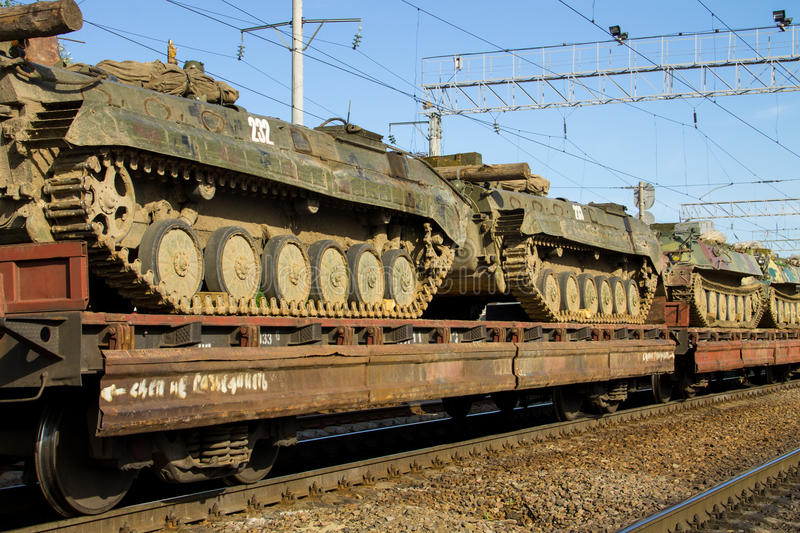 Cargo train carrying military tanks on railway flat wagons. Cargo train carrying military tanks on the railway flat wagons stock photos