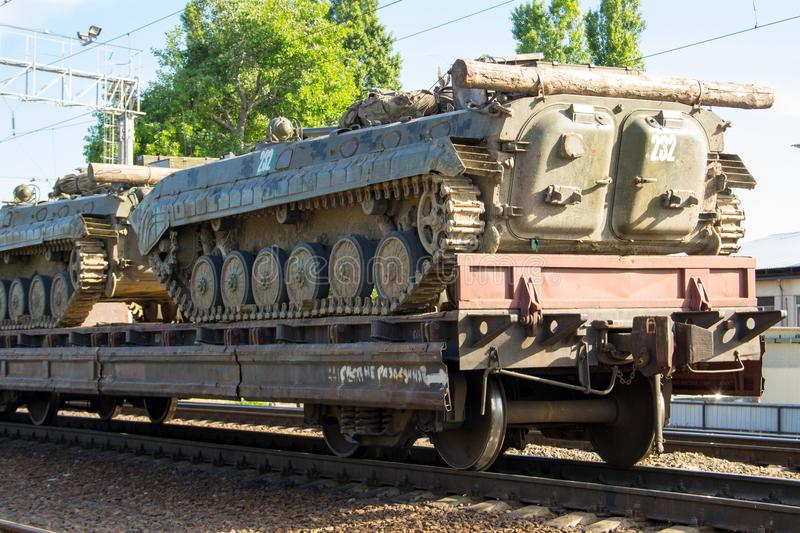 Cargo train carrying military tanks on railway flat wagons. Cargo train carrying military tanks on the railway flat wagons stock image