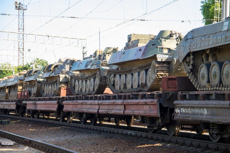 Cargo train carrying military tanks on railway flat wagons. Cargo train carrying military tanks on the railway flat wagons royalty free stock photos