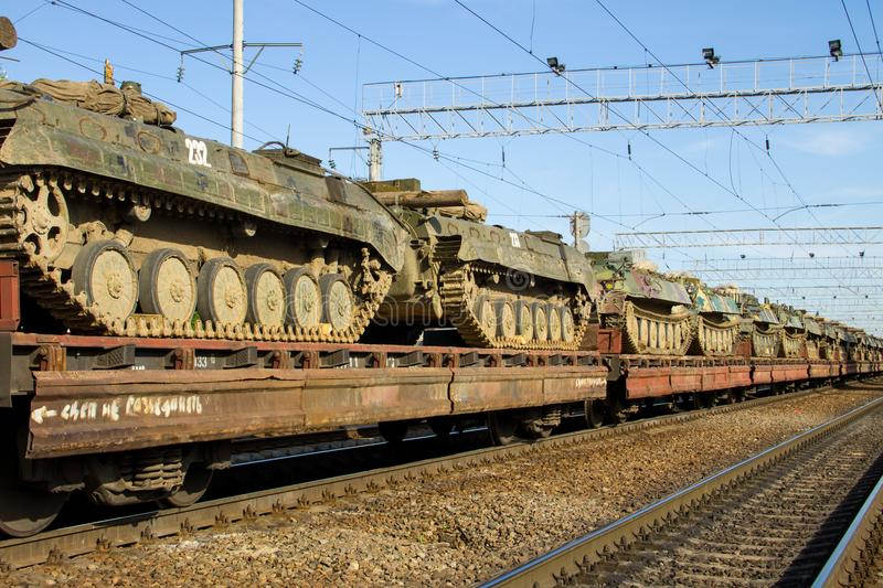 Cargo train carrying military tanks on railway flat wagons. Cargo train carrying military tanks on the railway flat wagons royalty free stock images