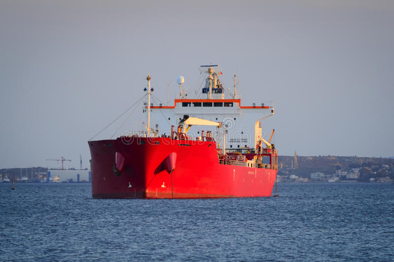 Cargo vessel at anchorage. View of a red cargo vessel at an anchorage, Greece royalty free stock photos