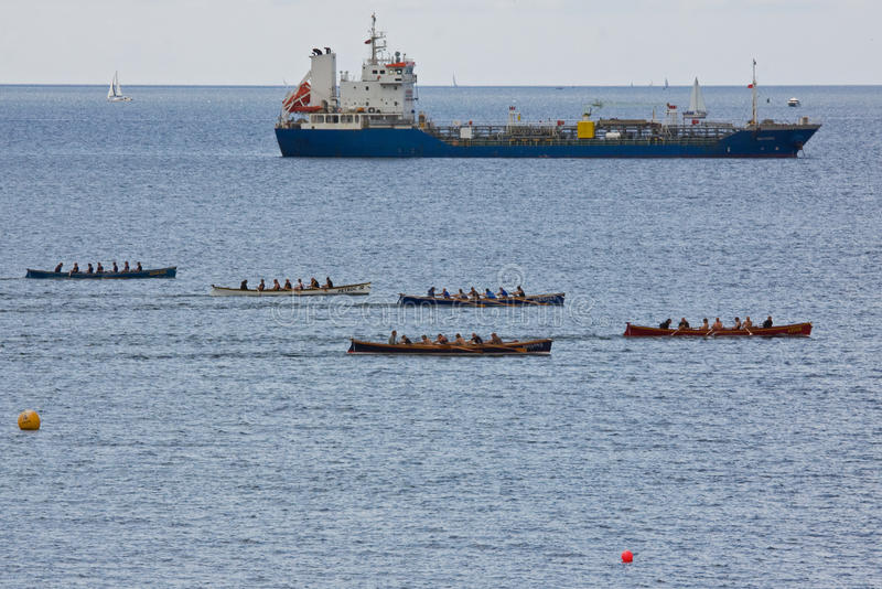 Cargo Vessel and Gig Racers off Falmouth UK. FALMOUTH , ENGLAND - JUNE 11: Teams in the Falmouth Gig Club sprint regatta in Falmouth Harbour, England on June 11 royalty free stock image