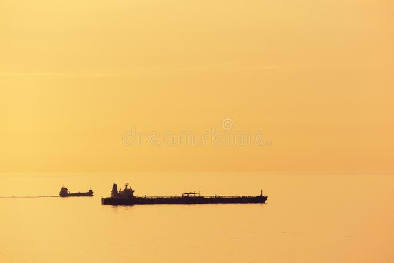 Cargos au coucher du soleil avec la mer calme photos libres de droits