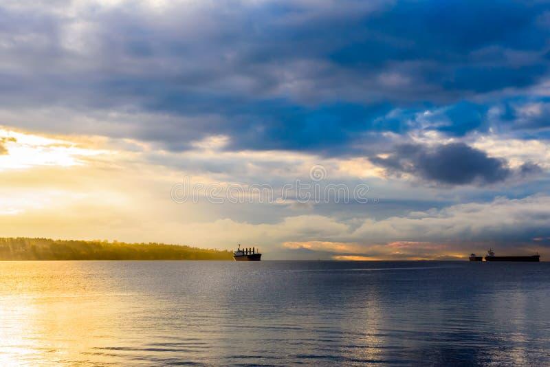 Cargos au coucher du soleil nuageux dans la baie photo libre de droits