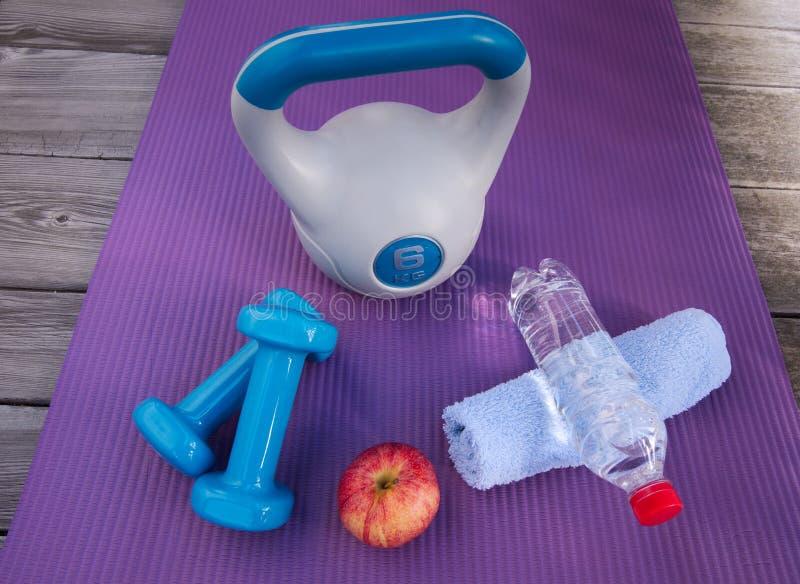 Cargue el entrenamiento con una campana y pesas de gimnasia de la caldera, que un bocado sano y porciones de agua fotos de archivo