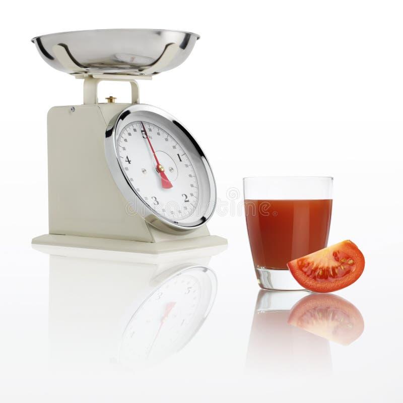 Cargue la escala con el vidrio del jugo de tomate aislado en el fondo blanco imagenes de archivo