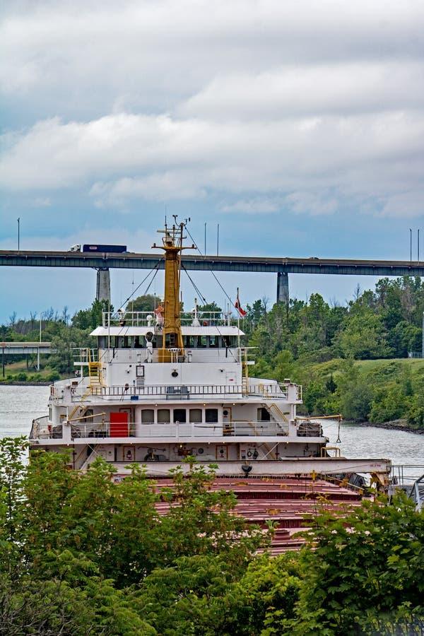 Carguero de Great Lakes alrededor a ir debajo del puente de la carretera foto de archivo libre de regalías