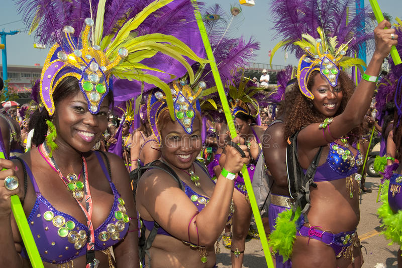 Caribana Parade. TORONTO, ONTARIO, CANADA - AUGUST 4, 2012: female participants, smiling, dressed in costumes, performing during annual Caribana Parade (North stock image